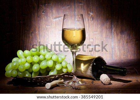 Wine bottles, bunch of grapes and glass of white wine on old wooden background - stock photo