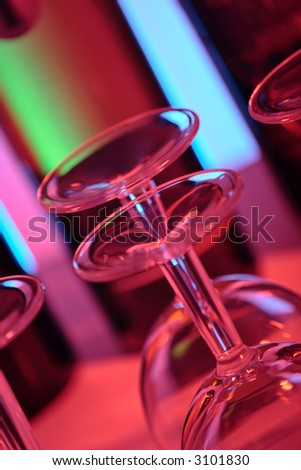 wine bottles in a bar with colorful lighting, shallow depth of field - stock photo