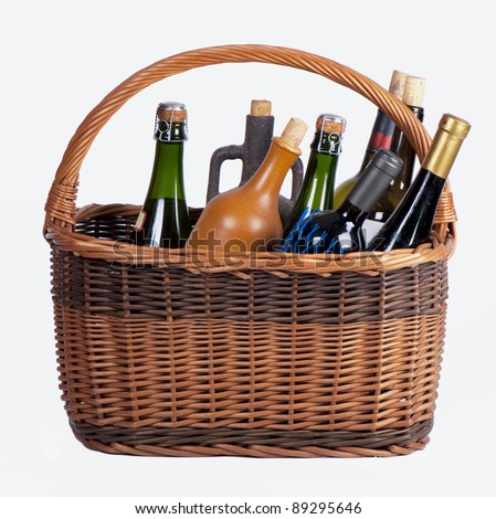 Wine bottles in a basket on a white background - stock photo