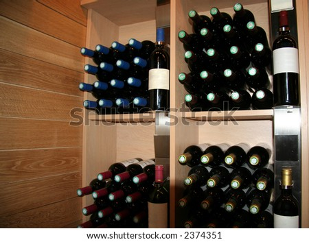 wine bottles in a rack - saint-emilion, france - stock photo