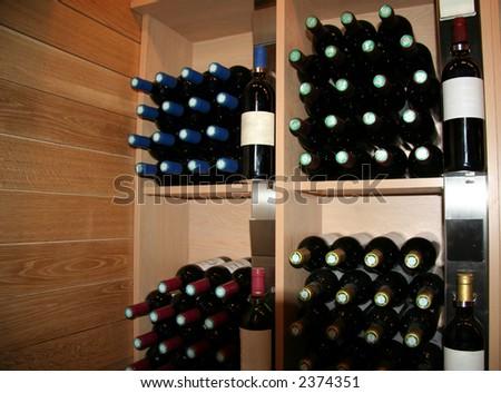 wine bottles in a rack - saint-emilion, france - stock photo