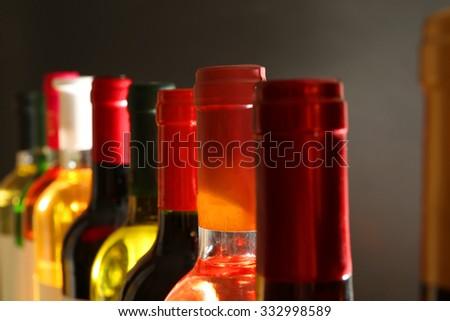 wine bottles in a row on dark grey background - stock photo