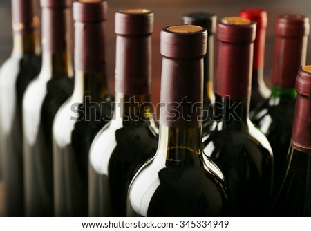 Wine bottles in a row on wooden background, close up - stock photo