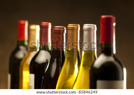 Wine bottles in a row with limited depth of field - stock photo