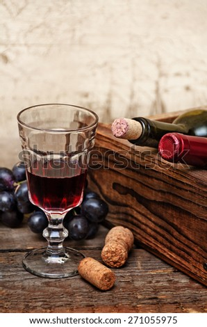 Wine bottles in wooden box, crystal glass with red wine and grapes are on the wooden background - stock photo