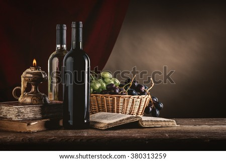 Wine bottles, old books, candle and ripe grapes in a basket on a rustic wooden table, still life - stock photo
