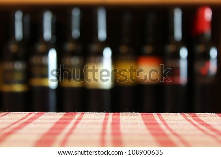 Wine bottles on a shelf in the foreground tablecloth shot with limited depth of field - restaurant background - stock photo