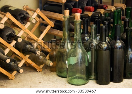 Wine bottles on floor and on wine rack - stock photo