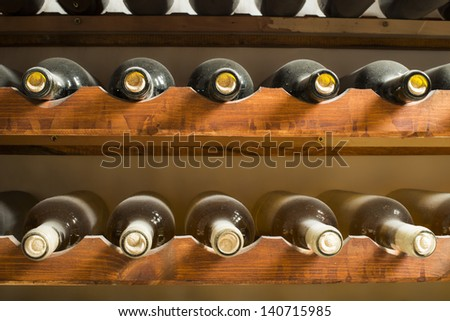 Wine bottles on shelf. Wine cellar. Close up wine bottles. - stock photo
