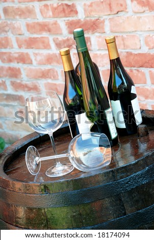 Wine bottles over barrel - stock photo