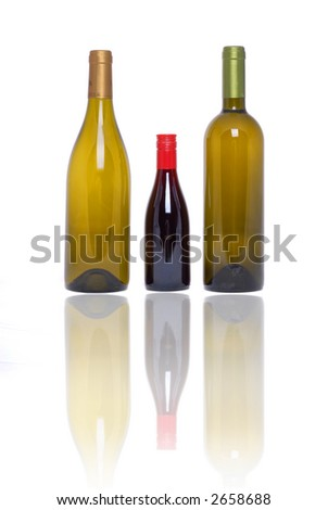 Wine bottles reflected on glass table top - stock photo