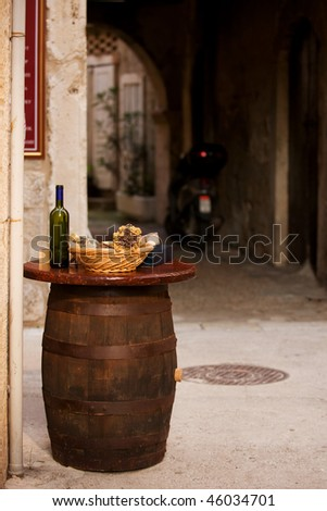 Wine bottles with bread on the top of the barrel in Trogir, Croatia - stock photo