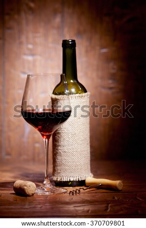 Wine bottles with glass on old wooden background - stock photo