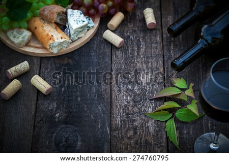 Wine bottles with grape leaves on wooden background with copy space - stock photo