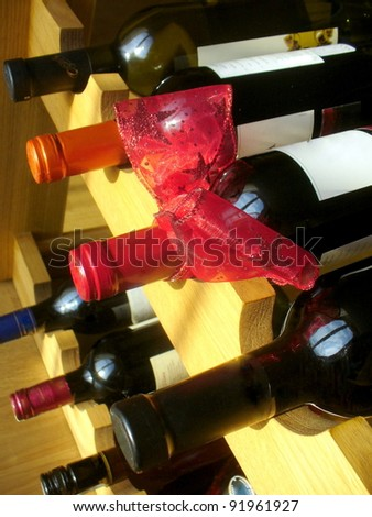 wine bottles with red ribbon stacked on wooden racks