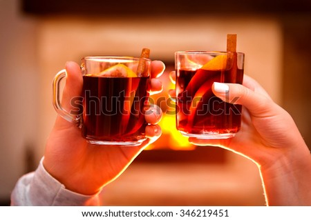 Wine by the fireplace, glasses of mulled wine. - stock photo