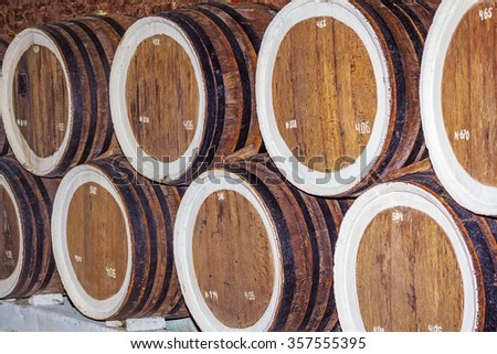 Wine cellar full of wooden barrels of wine - stock photo