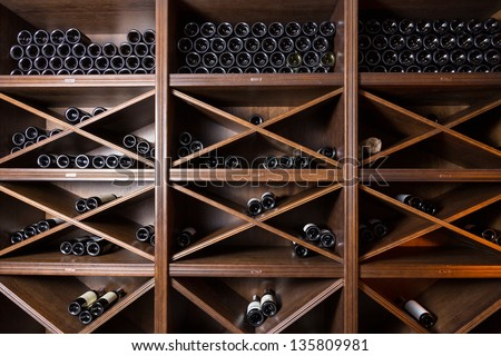 Wine cellar with bottles on wooden shelves - stock photo