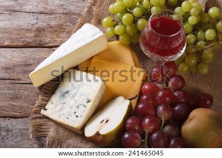 Wine, cheese and fruit on the table close-up. horizontal view from above