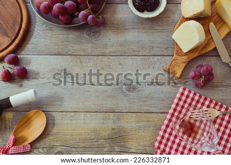 Wine, cheese and grapes on wooden table. View from above with copy space - stock photo