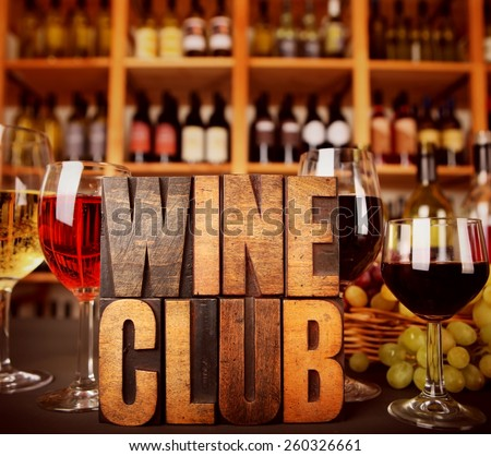 Wine Club in Vintage Letterpress letters in front of wine racks with wine and grapes - stock photo