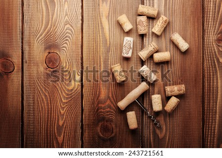 Wine corks and corkscrew over rustic wooden table background. View from above with copy space - stock photo