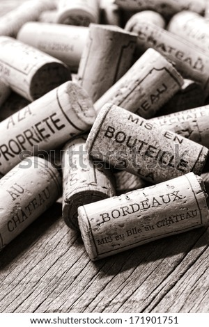 Wine corks from opened bottles with generic French winemaker wording naming local bottling at the castle or at the property in a loose pile on an old weathered vineyard cellar wood table in France - stock photo