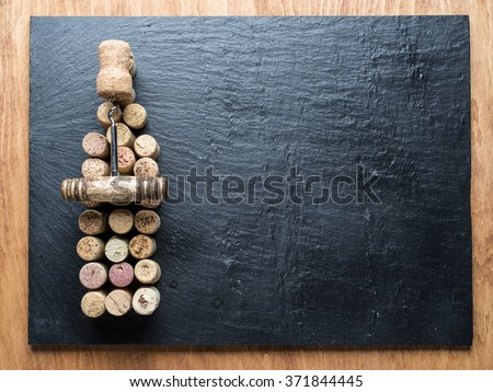 Wine corks in the shape of wine bottle on the graphite background. - stock photo