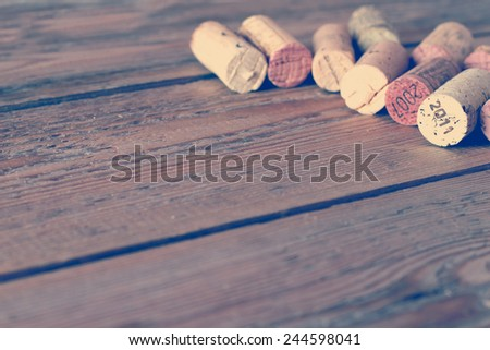 Wine corks lying on a wooden table. Vintage style, toned image. Selective focus. Copy space background - stock photo