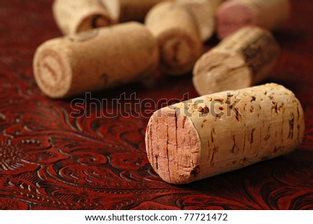 Wine corks on burgundy colored textured leather.  Macro with extremely shallow dof. - stock photo