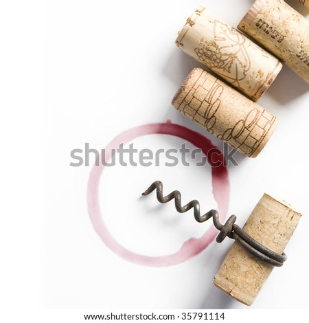 Wine corks, small corkscrew and round, red wine stain on white table cloth - stock photo