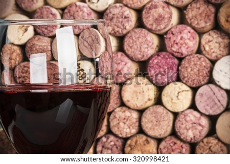 wine corks through a glass of red wine. Focus on the glass - stock photo