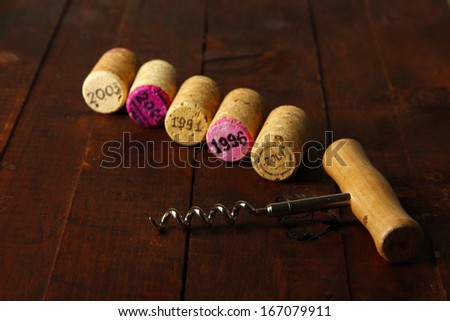 Wine corks with corkscrew on wooden table close-up - stock photo