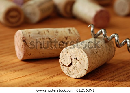 Wine corks with corkscrew on wooden table in warm natural lighting.  Macro with extremely shallow dof. - stock photo