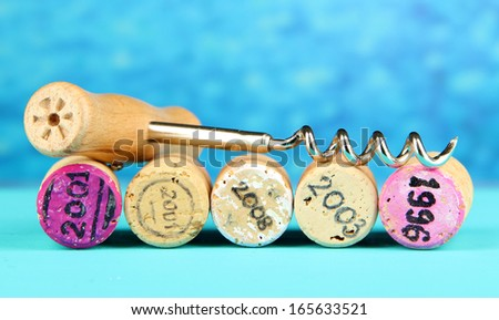 Wine corks with corkscrew on wooden table on blue background - stock photo