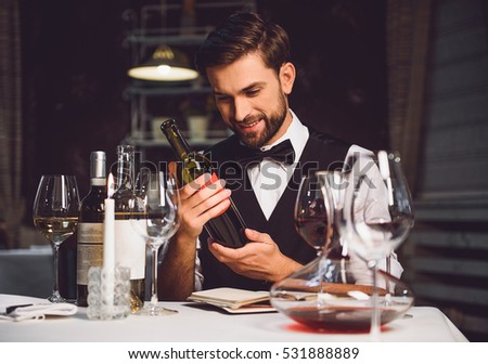 Wine critic holding bottle of scarlet drink with smile