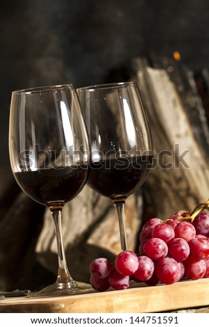 Wine cup, bottle grapes and cork over a wooden table.