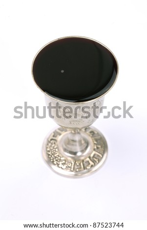Wine cup used for jewish Kiddush in Sabbath and Holidays. The writing on the bottom is a jewish wine blessing - stock photo