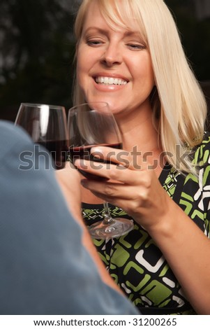 Wine Drinking Blonde Socializing with Man at an Evening Gathering. - stock photo