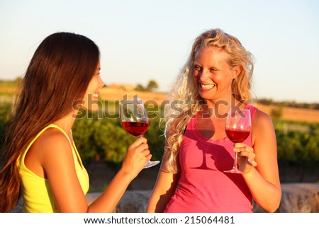 Wine drinking friends toasting drinks at vineyard. Two women cheering with a glass of rose or red wine in summer. - stock photo