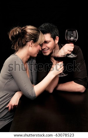 Wine drinking young couple flirting - stock photo