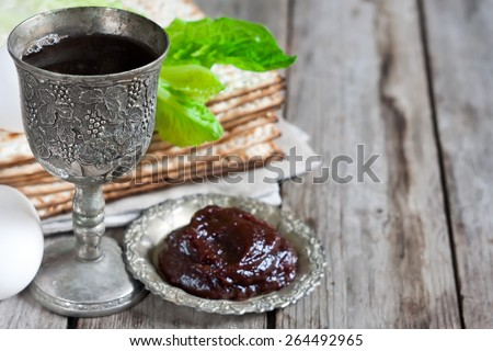 Wine, egg, bitter salad leaves, matzot and haroset - traditional jewish passover celebration elements. Copy space background. - stock photo