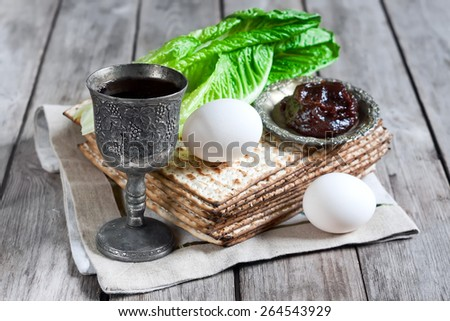 Wine, egg, bitter salad leaves, matzot and haroset - traditional jewish passover celebration elements. Selective focus. - stock photo