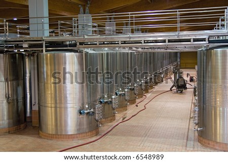 Wine Fermenting in huge vats in a famous wine cellar in spain. - stock photo