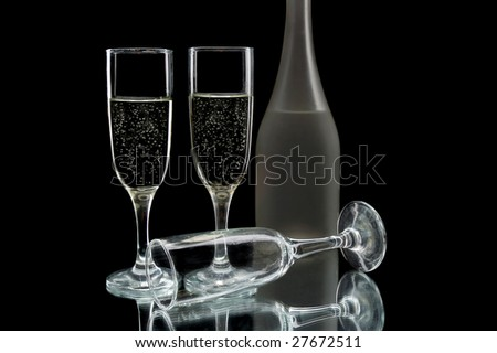 Wine flutes and wine bottle against a black background - stock photo