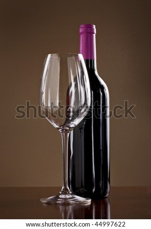 Wine glass and a bottle of red wine in a dimly lit cellar - stock photo