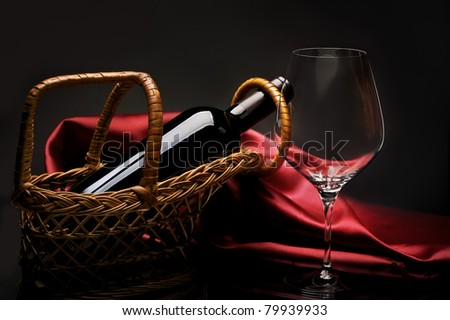 Wine glass and bottle of red wine in basket on background of red brilliant cloth. - stock photo