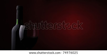 Wine glass and bottle on a dark red background with space for text - stock photo