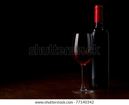 Wine glass and Bottle on a wooden table - stock photo