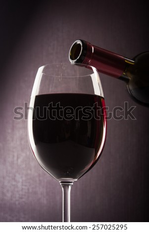 Wine glass and bottle on dark background